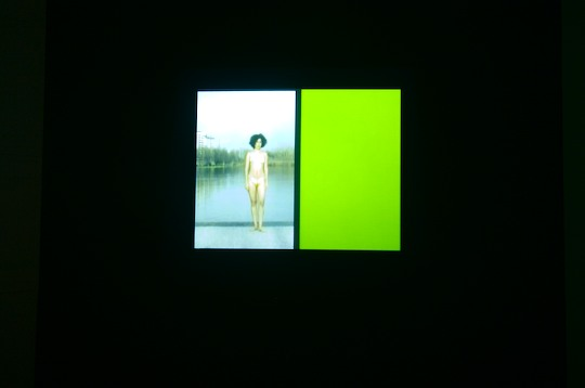 photo of video projecting woman in bikini next to a green rectangle of light