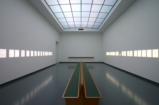 large white room with bench in centre and lightboxes along the walls and large skylight