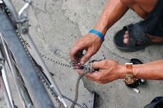 A mechanics hands replacing a bicycle deraileur