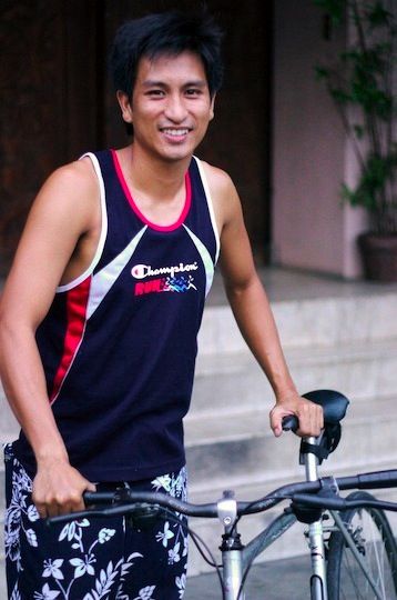 A Filipino man next to his bicycle