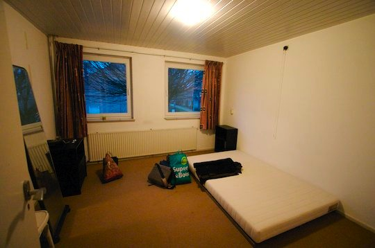 bare bedroom with mattress and two windows
