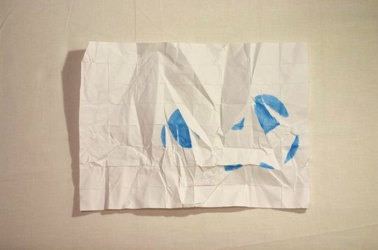 uncrumpled paper with blue fragments