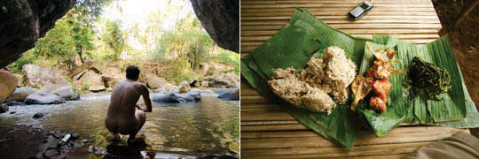 A naked man (me) kneeling by the river between two large boulders, food on a palm leaf