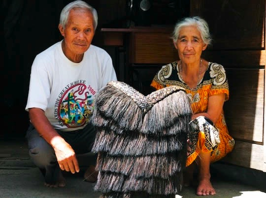 Photograph of two elderly people with the hunter backpack or bango in front of them