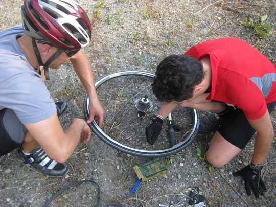 Two men fixing a flat tire on a bicycle
