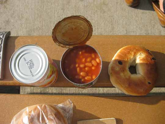 Can of beans  and a bagel on a park bench