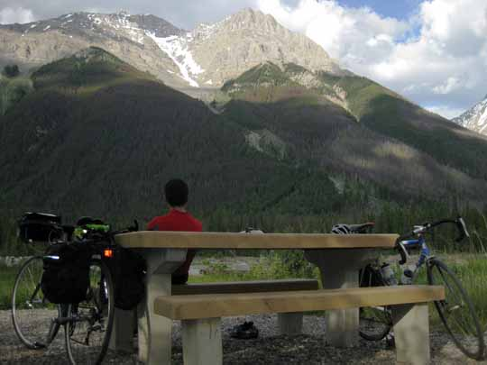 Man sitting at picnic table overlooking scenic mountains