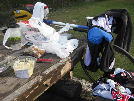 Picnic table with groceries, bicycle and shorts