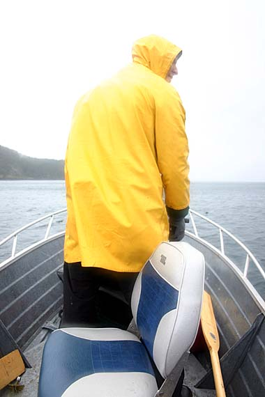 Man in yellow jacket standing in boat