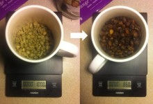 Photograph of coffee mug with green beans on left, roasted on right, Scale beneath mug indicates 100g of green, 85 of roasted