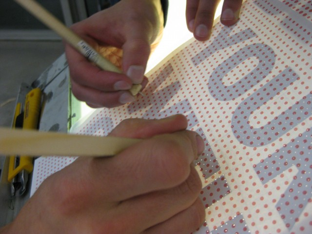 Hand perforating the hidden message.