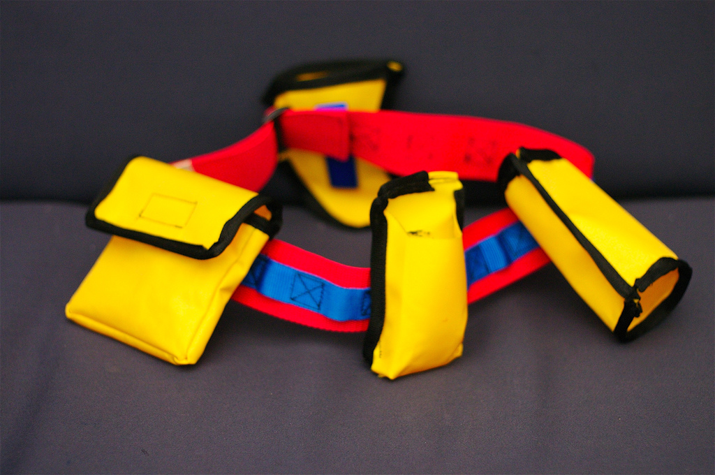 Yellow red and blue belt with pouches and holster on grey background.