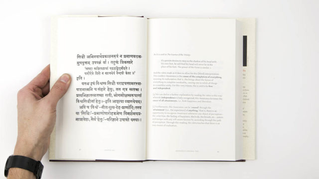Interior spread of hard cover book showing sutra on left, text on right